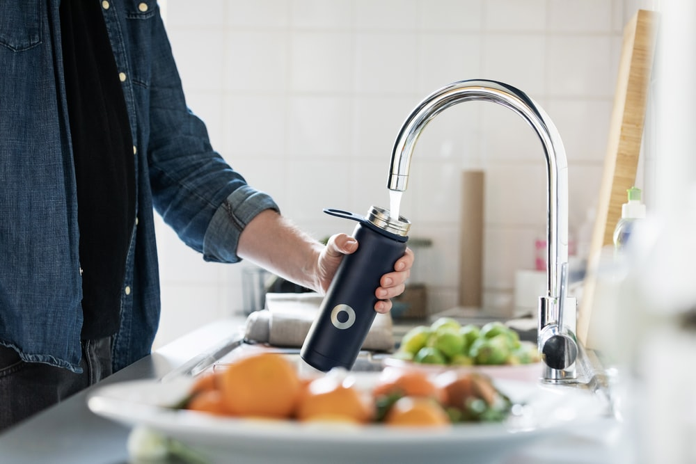 person holding stainless steel faucet