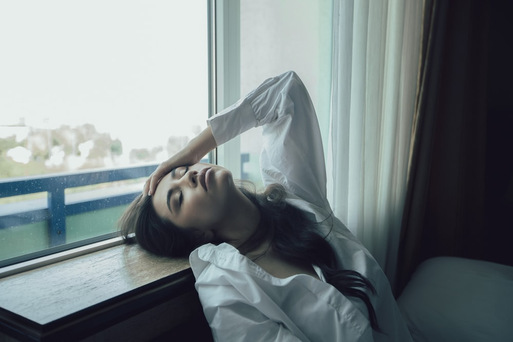 woman in white dress shirt lying on bed