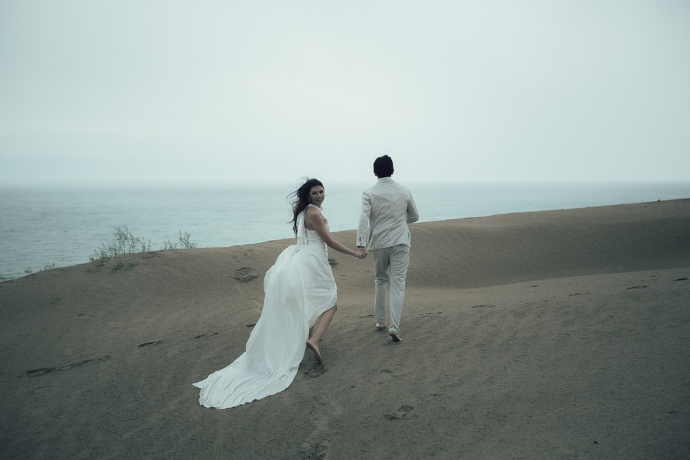 man and woman in white wedding dress walking on brown sand near body of water during