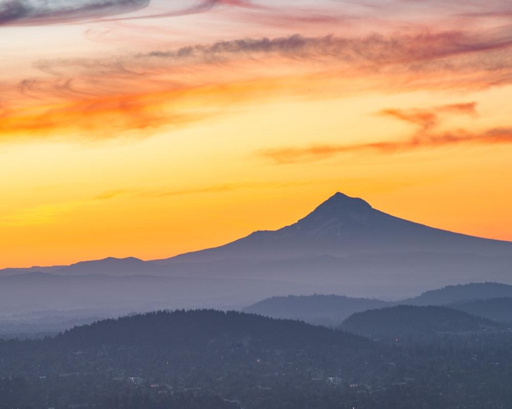 mountain range under orange and blue sky