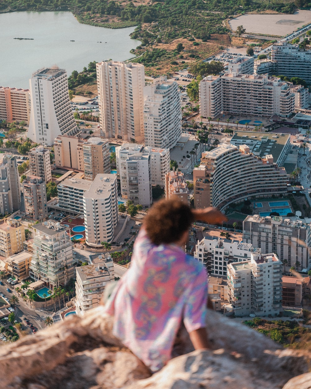 woman in pink and white floral shirt sitting on top of building looking at city buildings