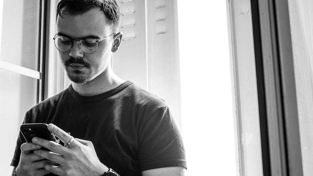 man in crew neck t-shirt wearing black framed eyeglasses