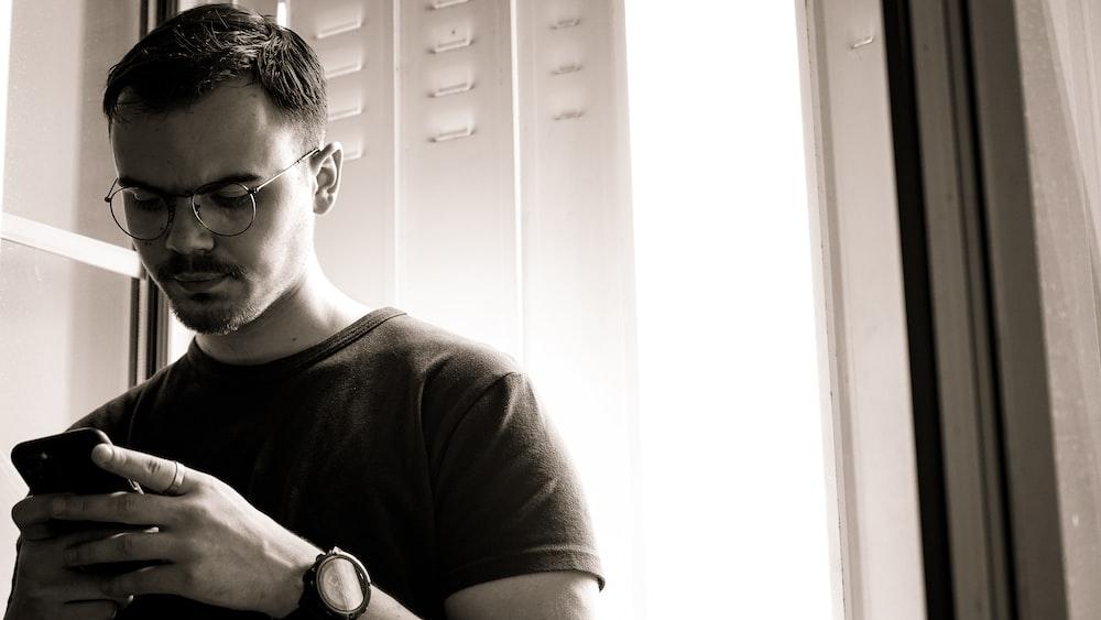 man in black crew neck t-shirt wearing black framed eyeglasses