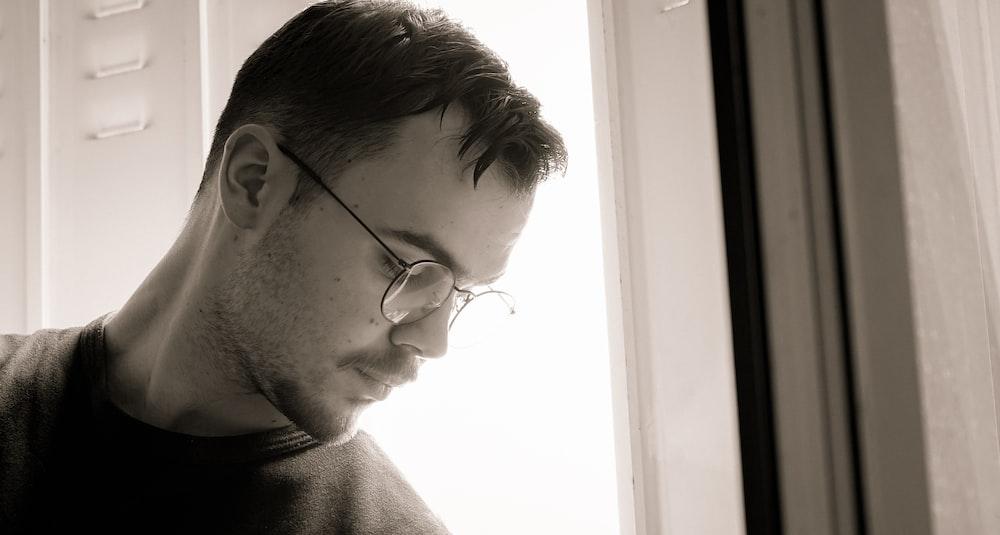 man in black framed eyeglasses and brown sweater