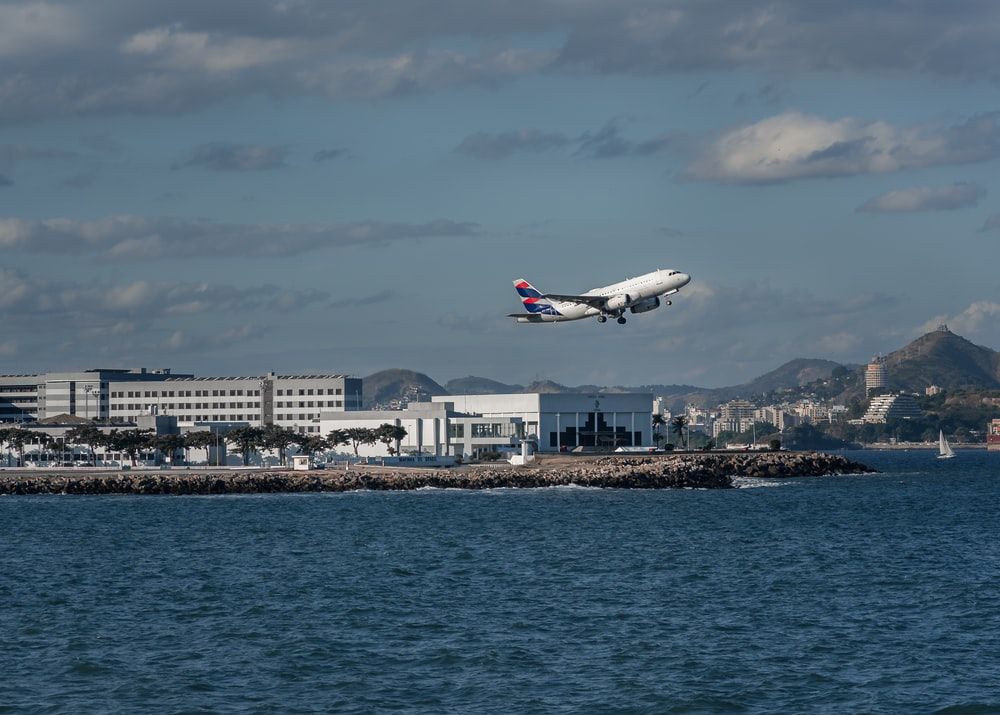 white passenger plane flying over city skyline during daytime