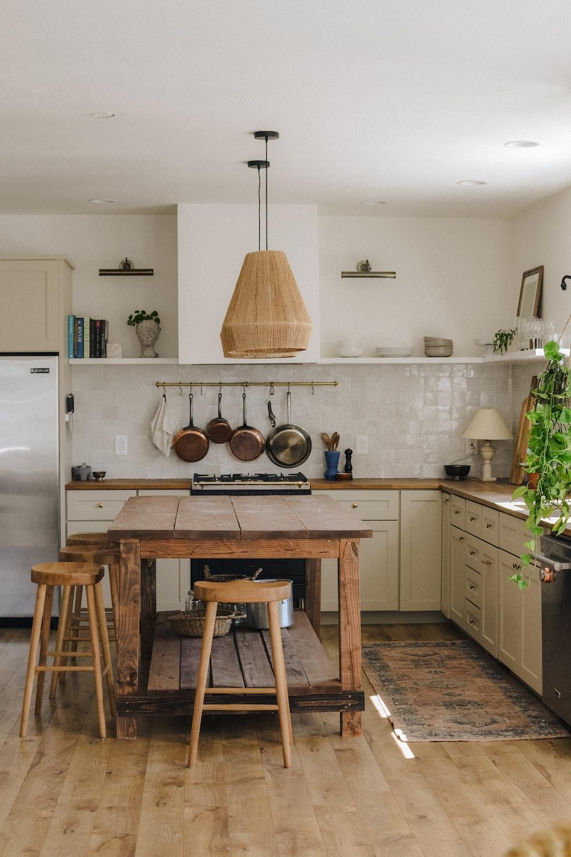 brown wooden seat beside white wooden kitchen cabinet