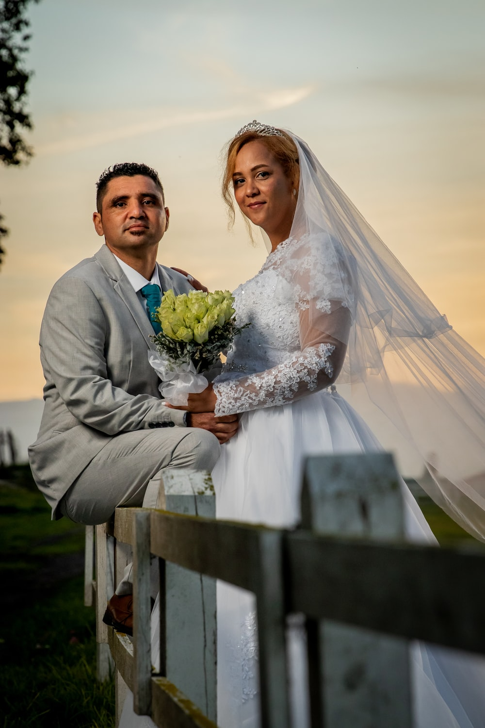 man in gray suit jacket holding bouquet of flowers beside woman in white wedding gown