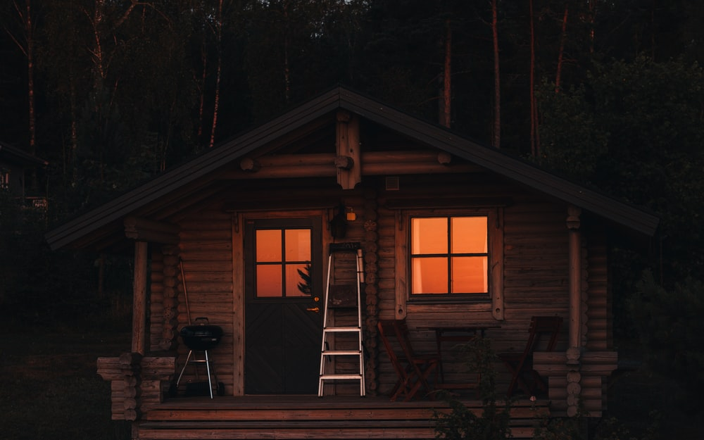 brown wooden house surrounded by trees during night time
