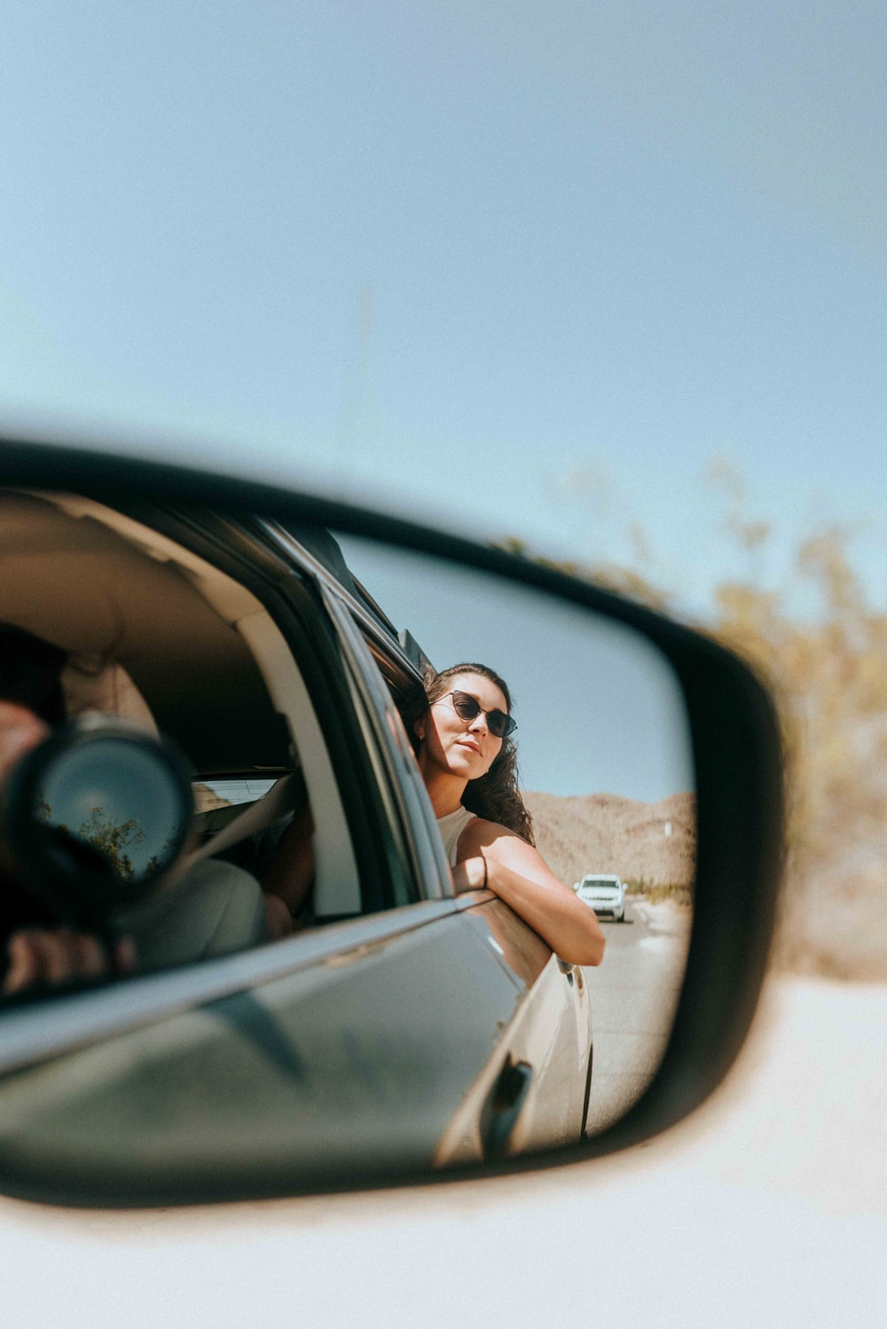 woman in white shirt and brown skirt wearing black sunglasses driving car during daytime