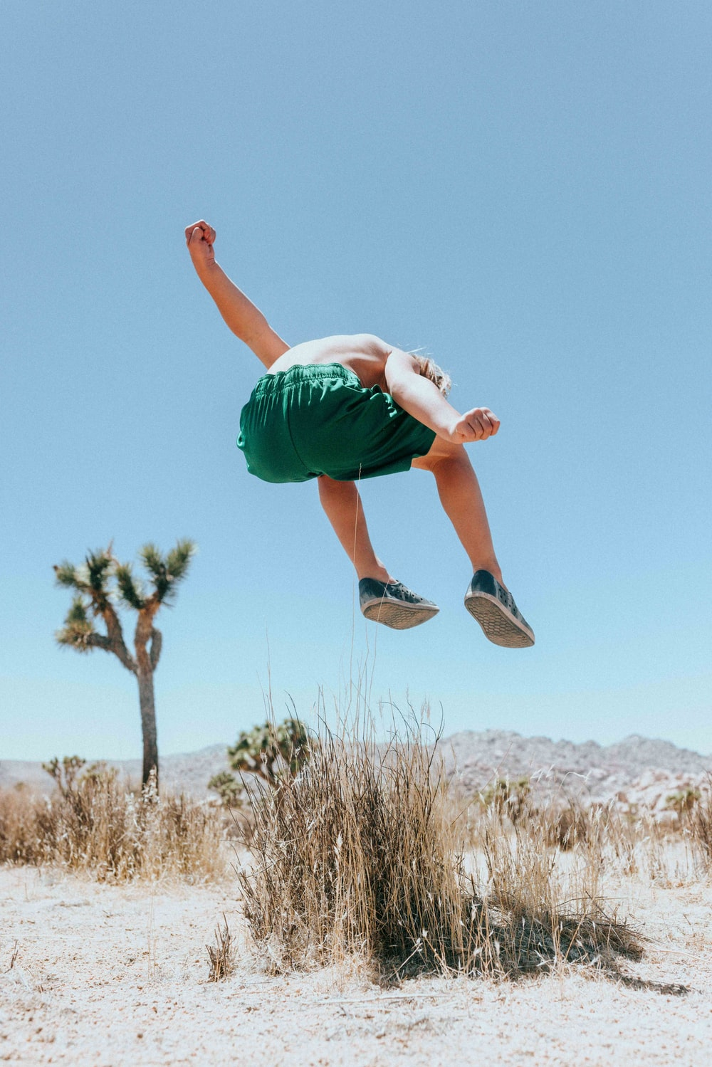 man in green t-shirt and green shorts jumping on brown grass field during daytime