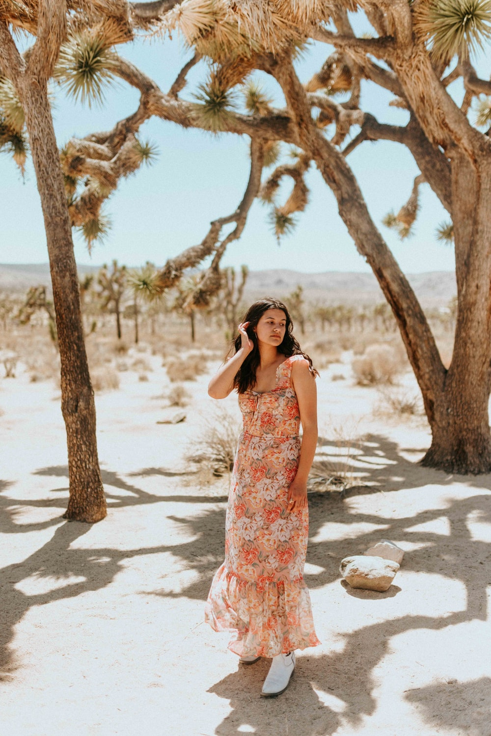 woman in white and red floral sleeveless dress standing on white sand during daytime