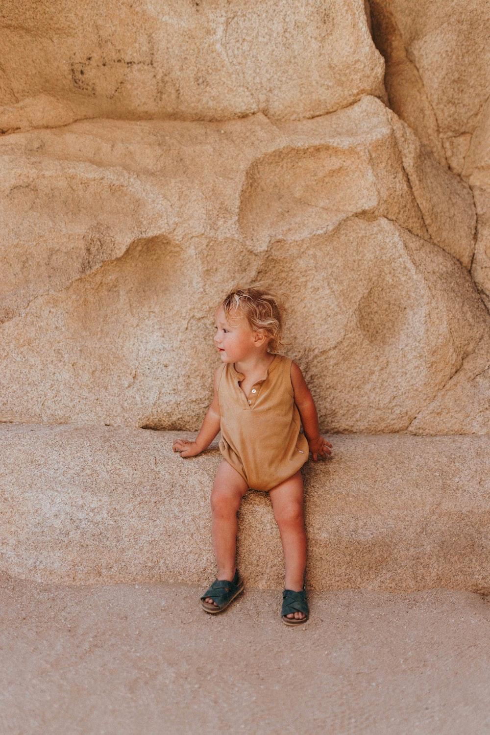 girl in brown dress sitting on brown concrete floor