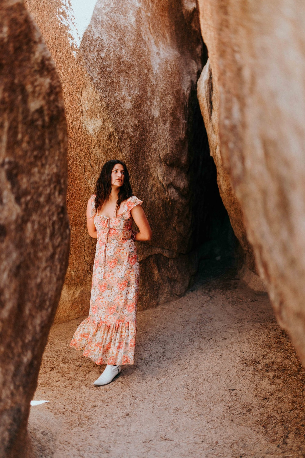 woman in white and pink floral dress leaning on brown rock