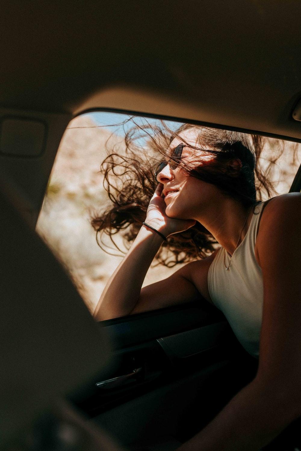 woman in white tank top sitting inside car during daytime