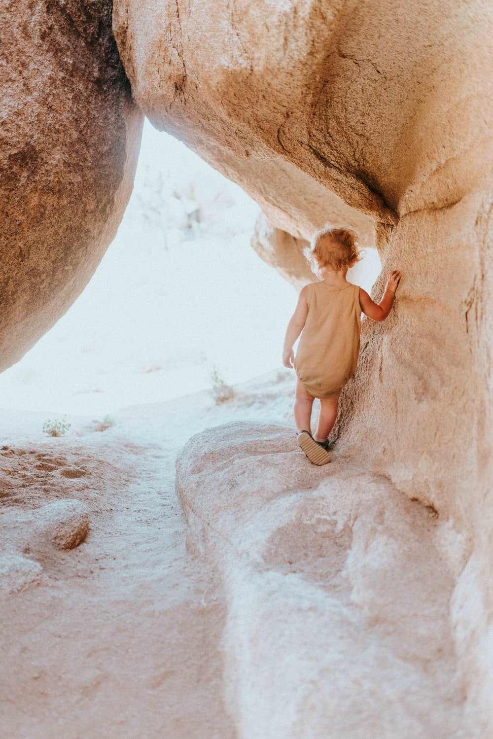 woman in white shirt and brown shorts climbing on brown rock
