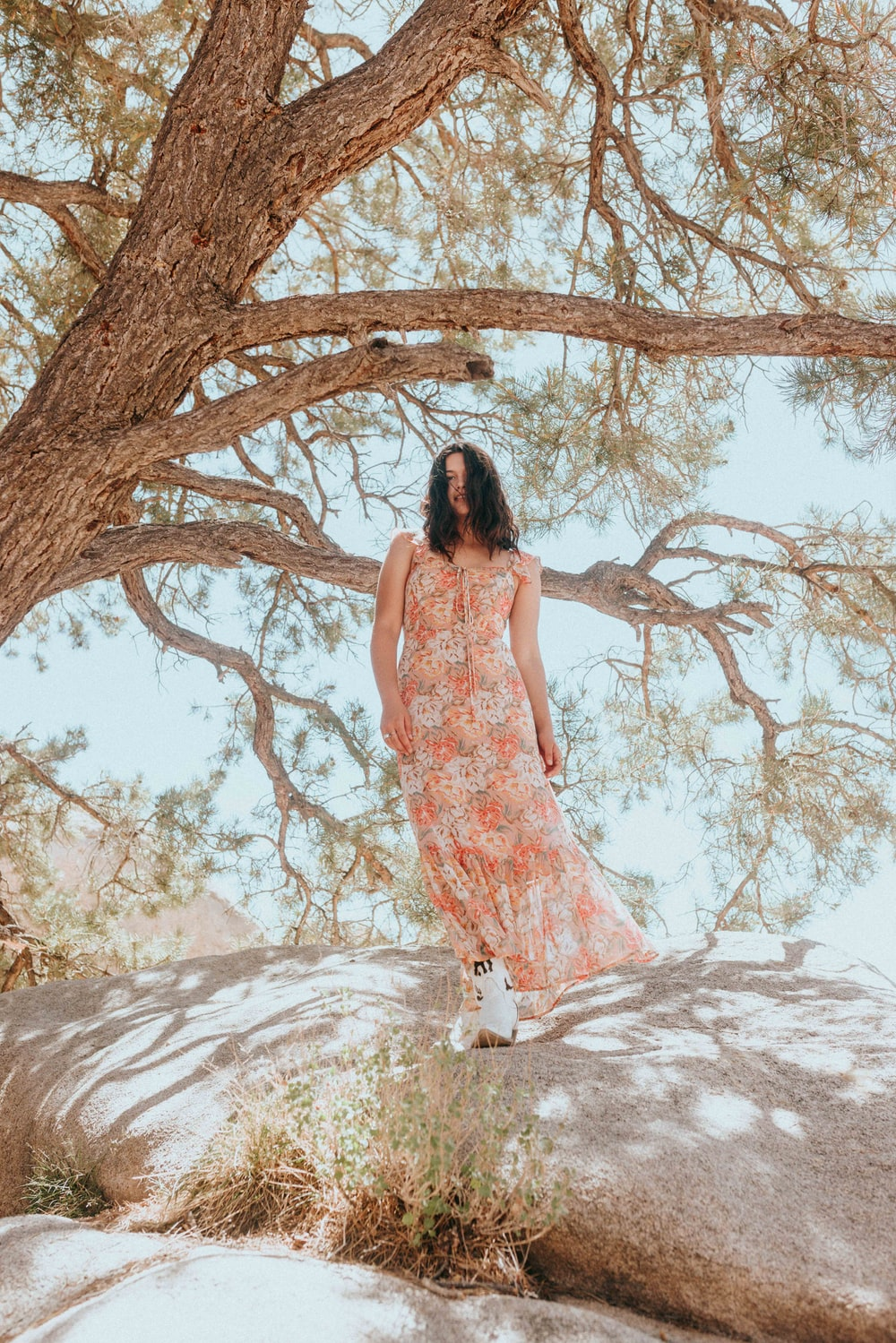 woman in white and pink floral dress standing under brown tree