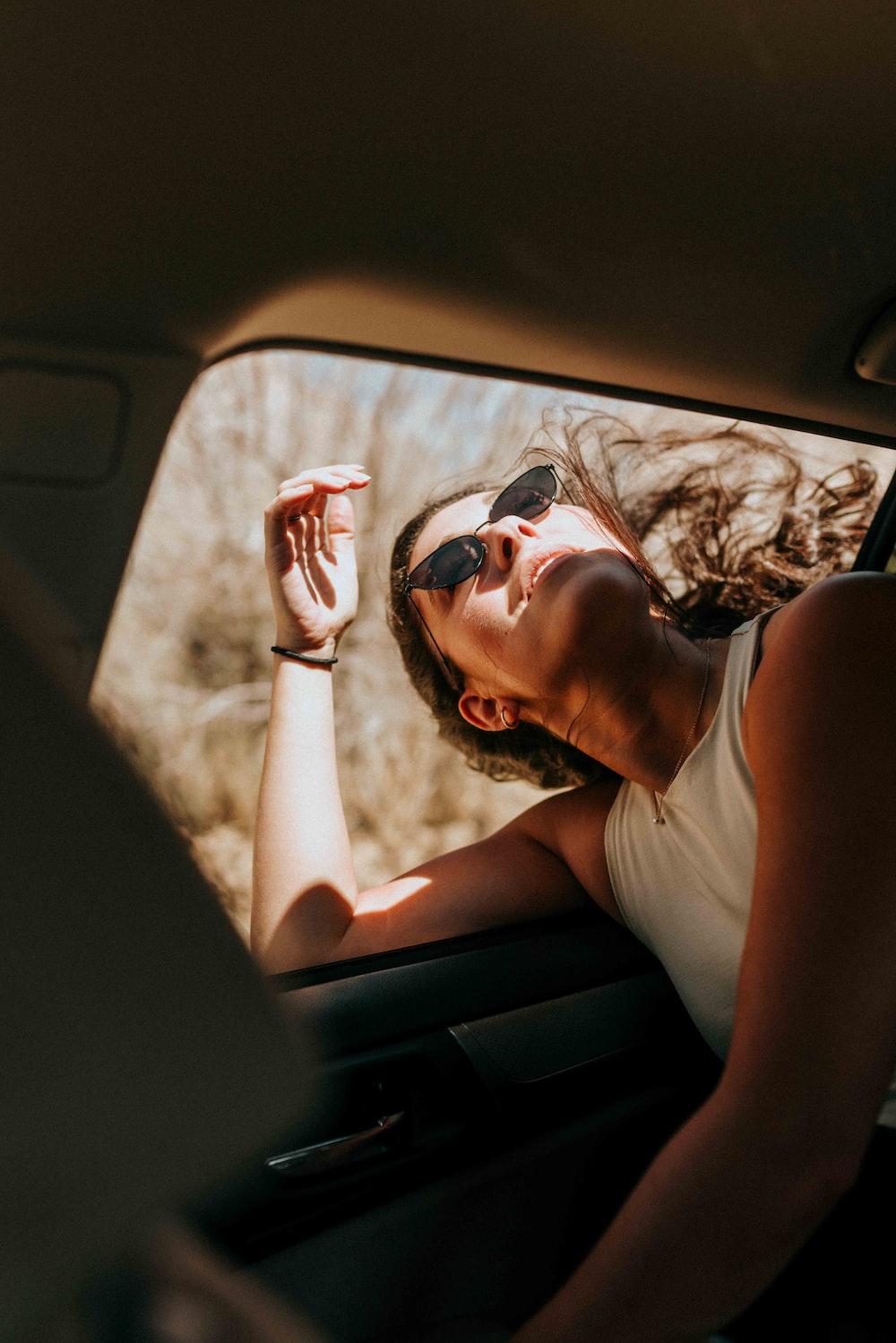 woman in white tank top wearing sunglasses sitting inside car