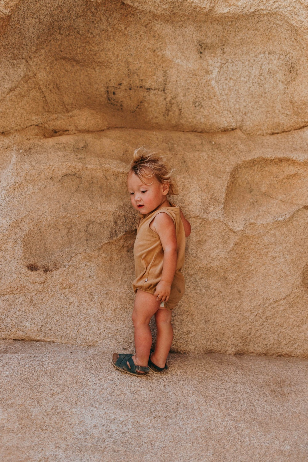 girl in brown sleeveless dress sitting on brown sand during daytime