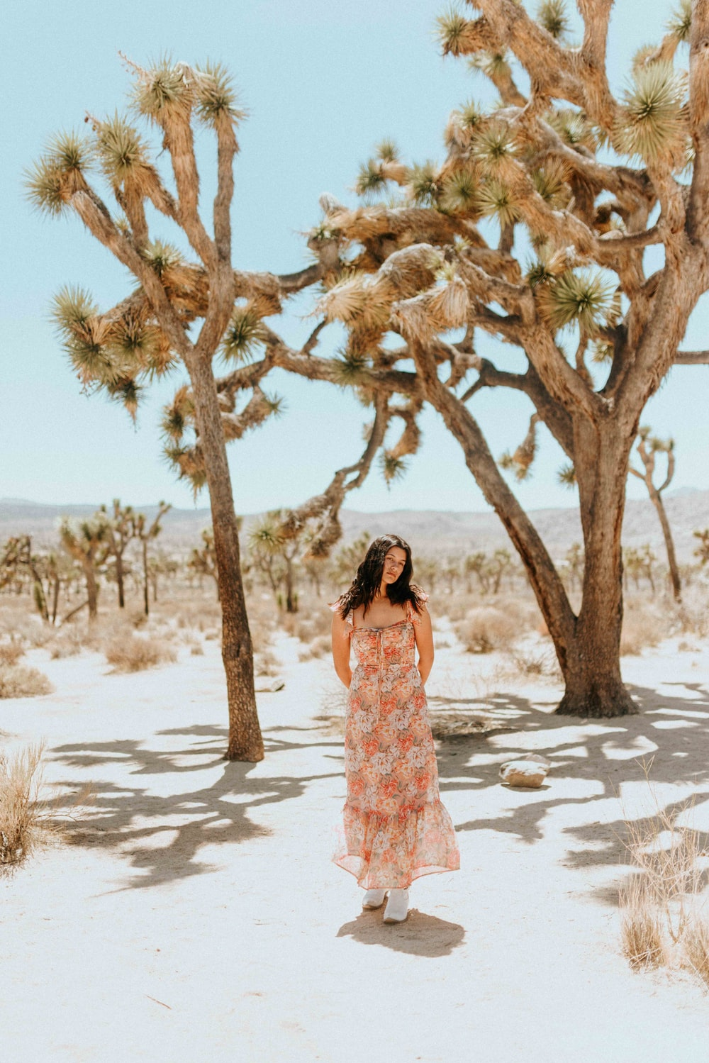woman in white and pink floral dress standing under brown tree during daytime