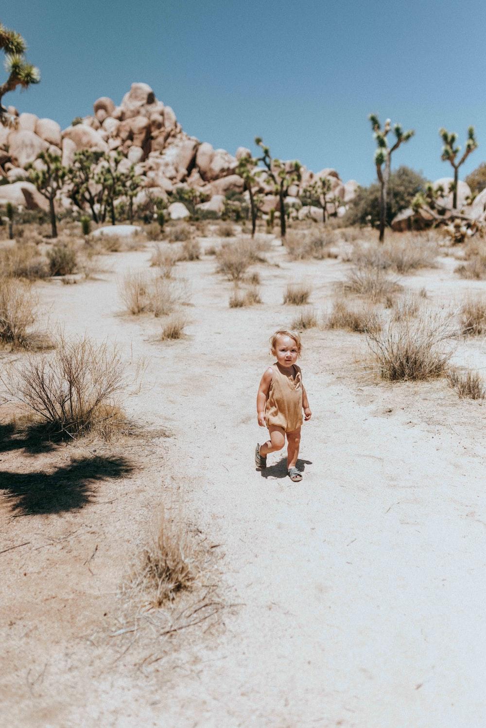 girl in brown dress running on white sand during daytime