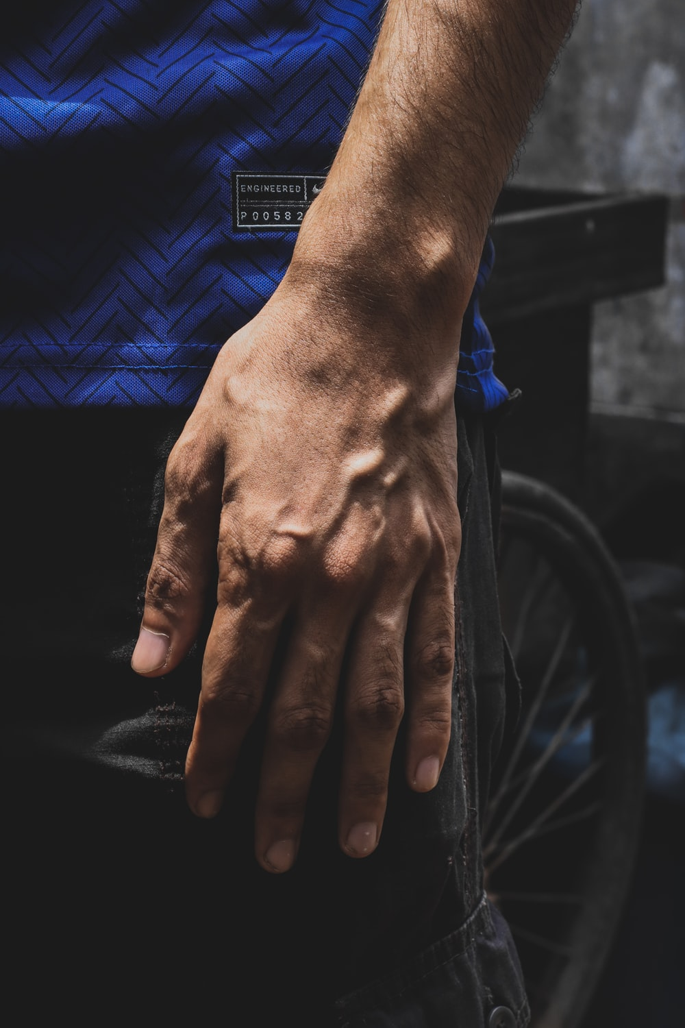 persons hand on black bicycle wheel
