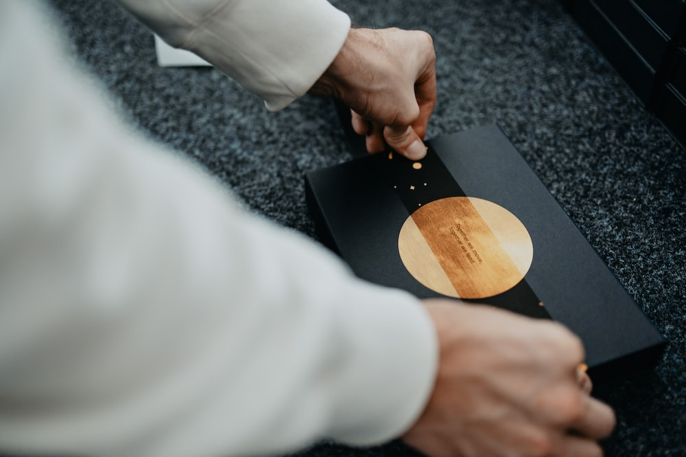 person holding brown wooden round plate