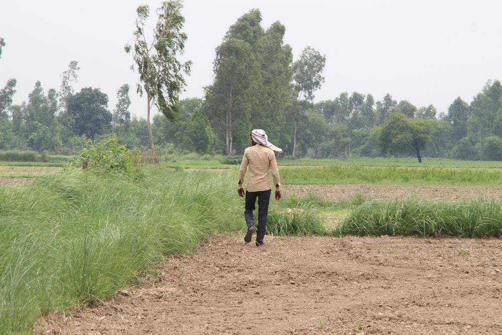 man in brown jacket walking on dirt road between green grass field during daytime