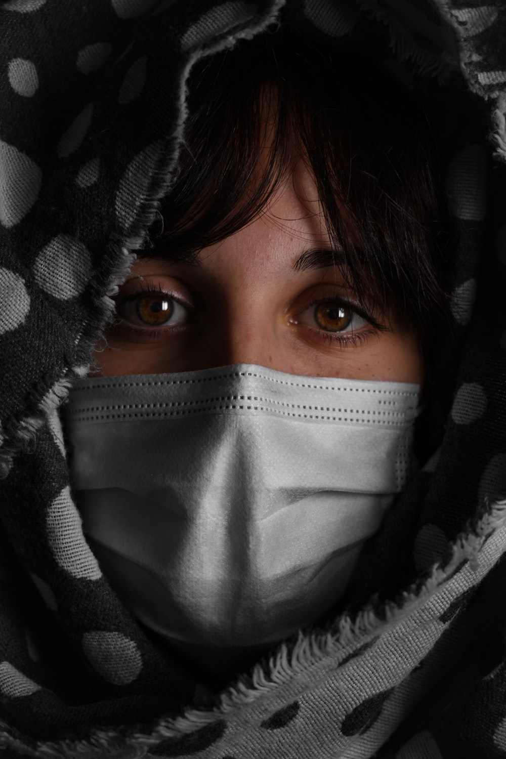 woman covering her face with black and white textile