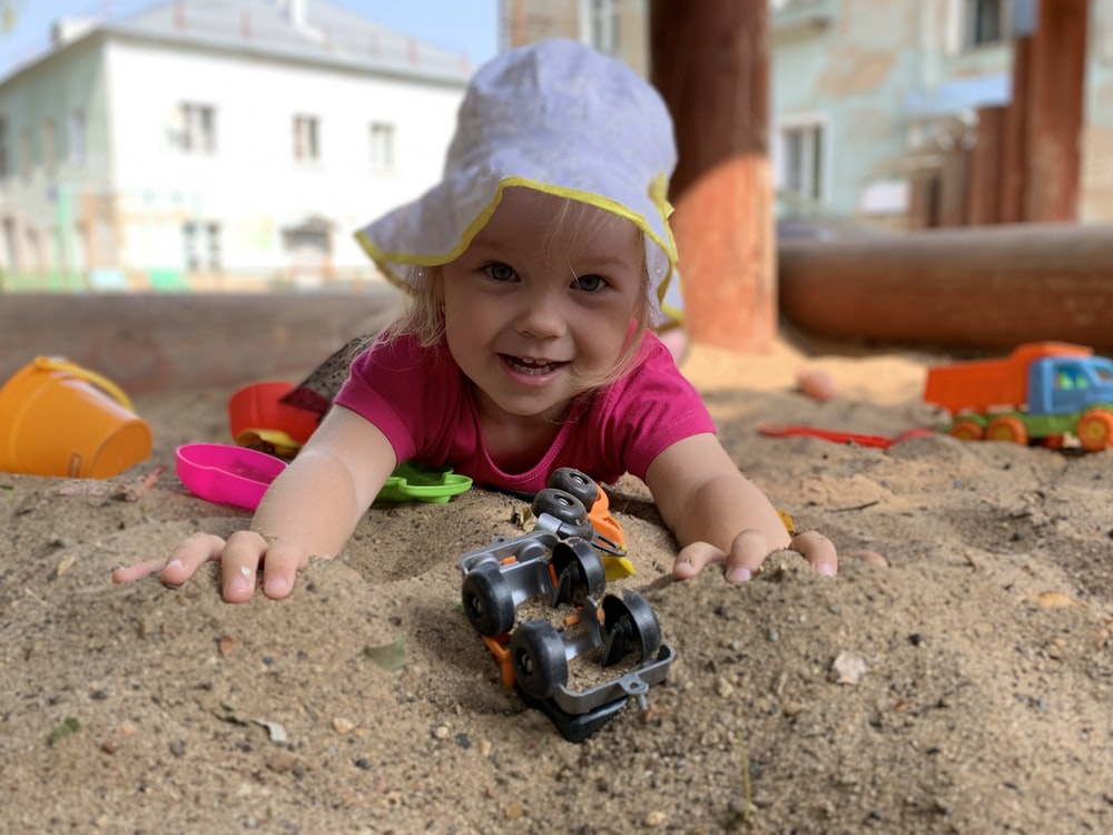 girl in white and green shirt playing with black toy car