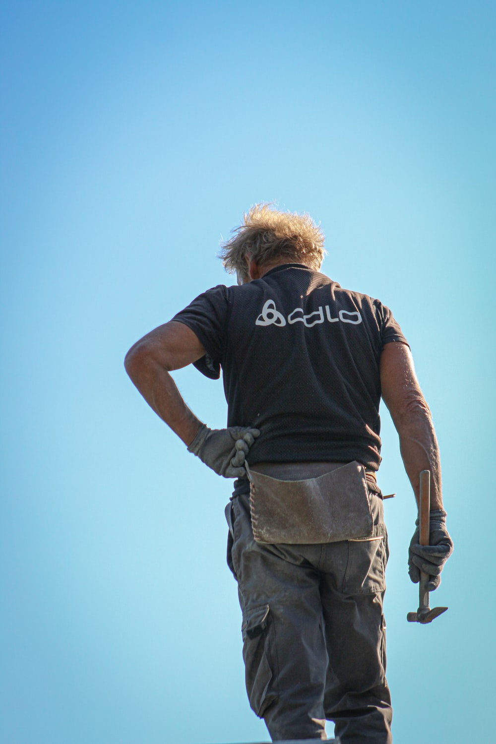 man in black t-shirt and gray cargo pants standing under blue sky during daytime