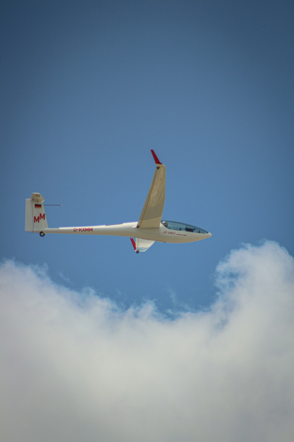 white and red airplane flying in the sky during daytime
