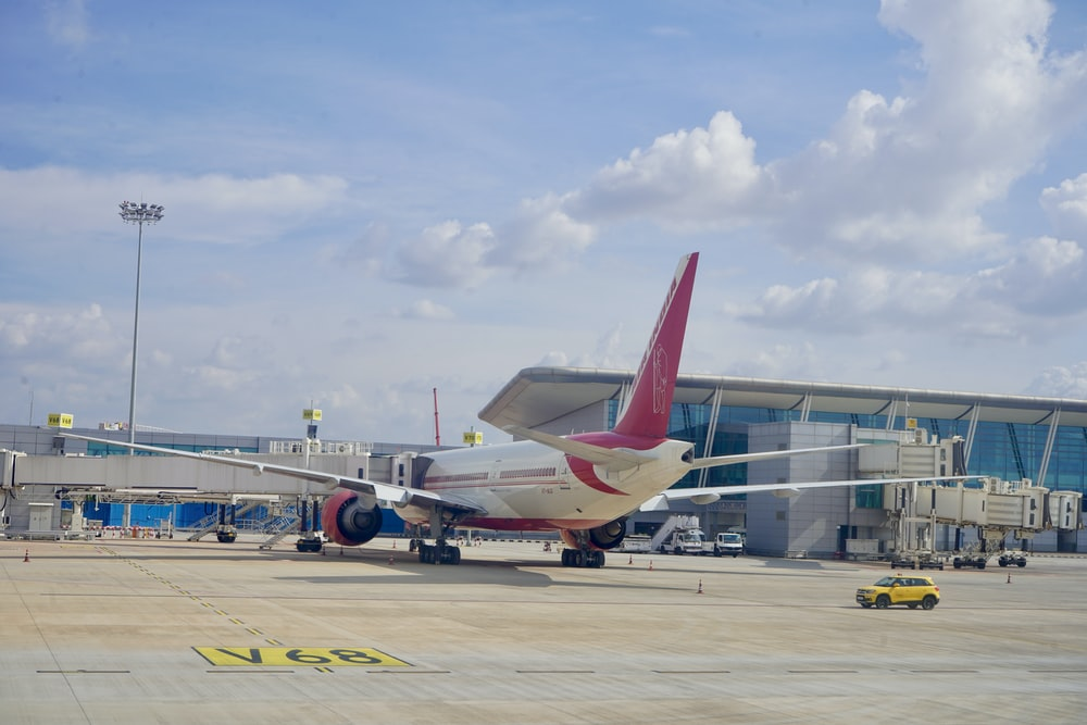white and red airplane on airport during daytime