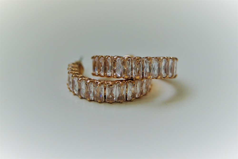 silver and gold bracelet on white surface