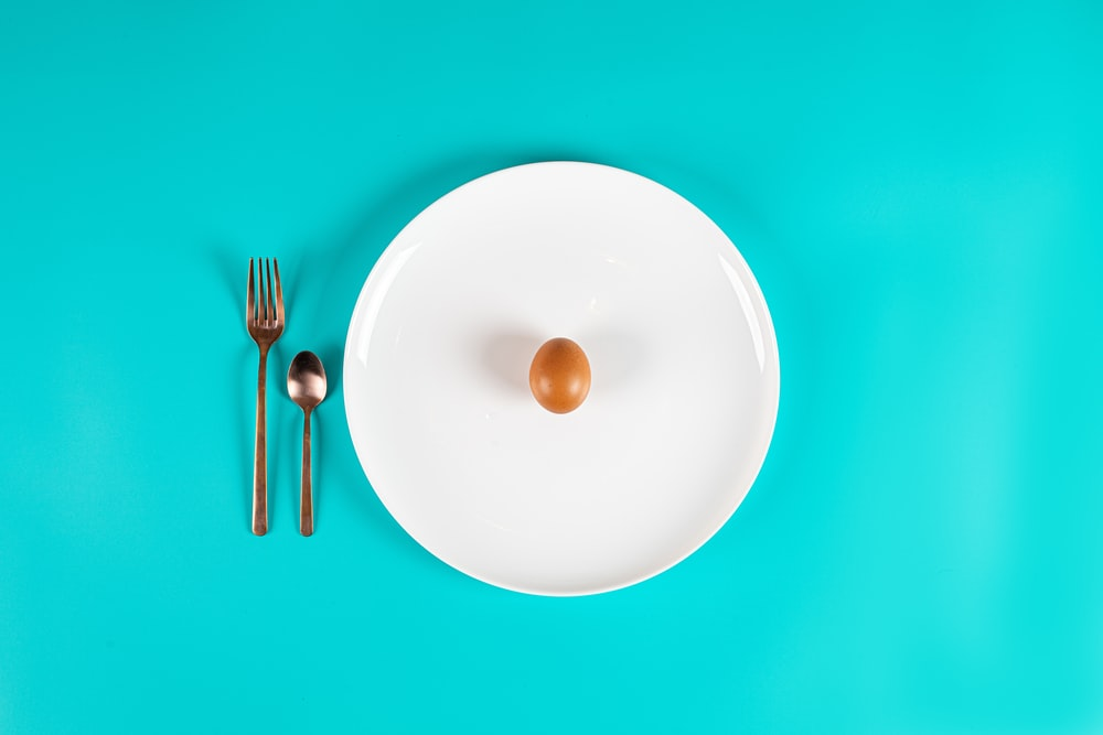 stainless steel fork and spoon on white round plate