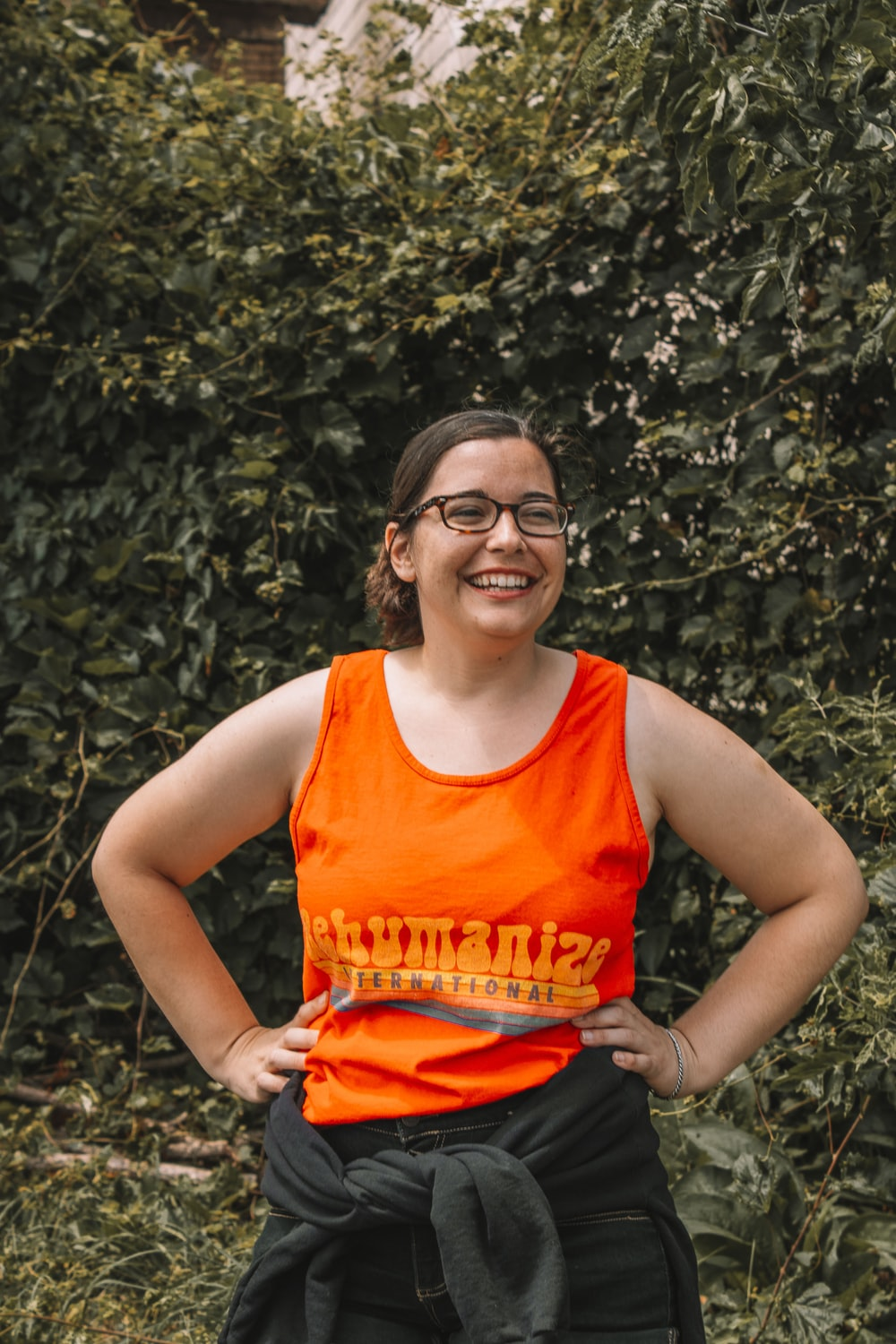 woman in orange tank top and red shorts smiling