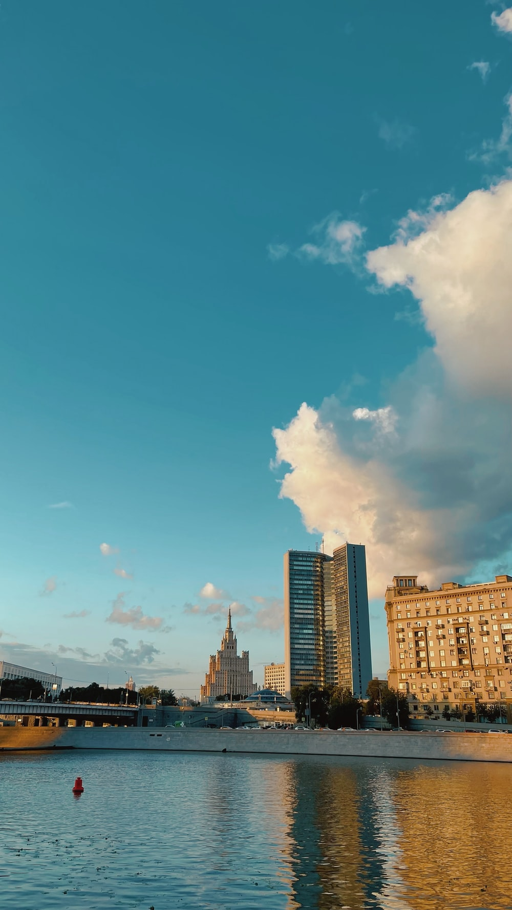 city buildings under blue sky and white clouds during daytime