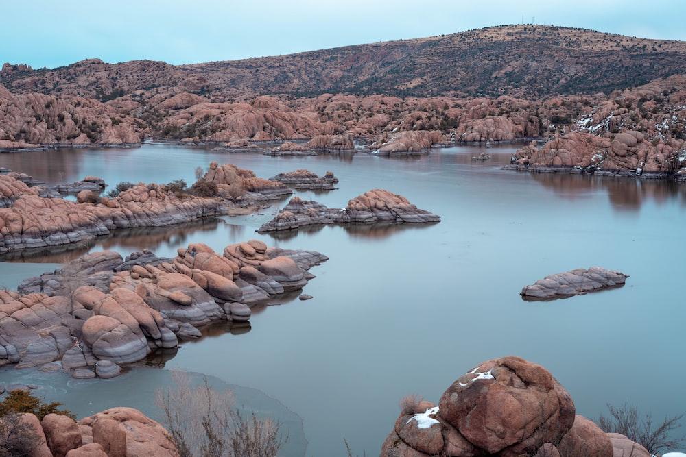 brown rock formation on lake during daytime