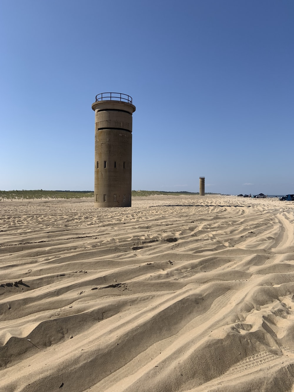 brown concrete tower on brown sand under blue sky during daytime