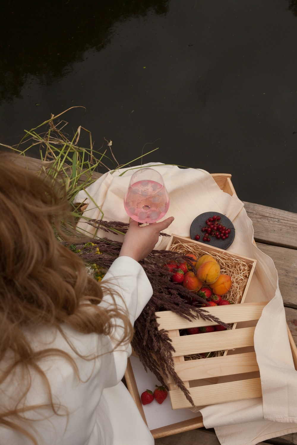 girl in white t-shirt sitting on brown wooden bench with fruits on brown wooden crate