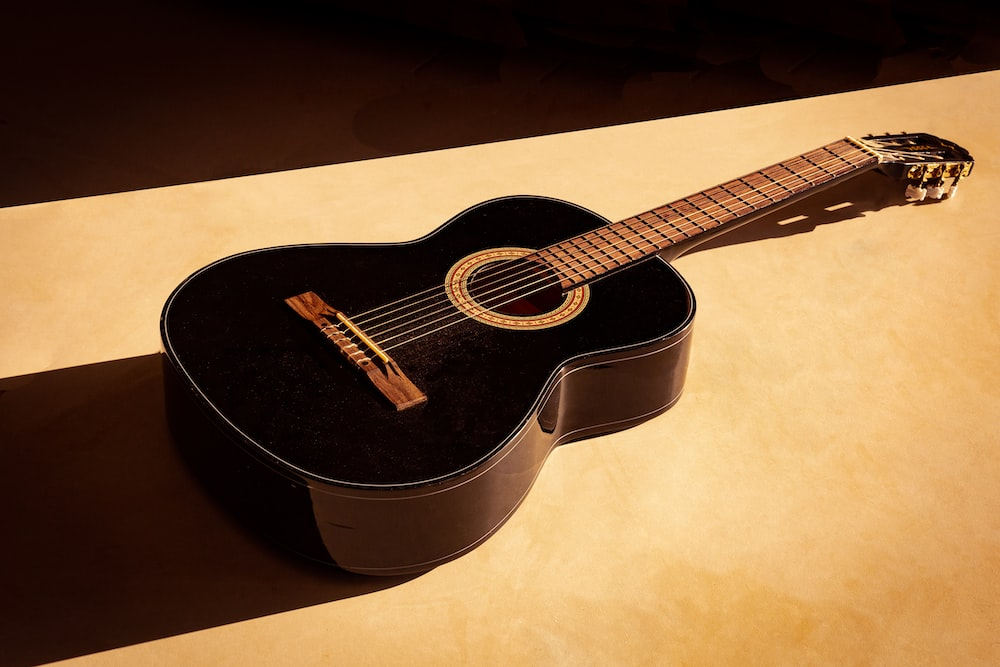 black acoustic guitar on white table