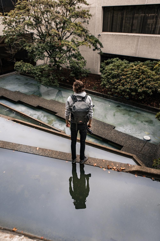 man in black jacket and black pants standing beside pool during daytime