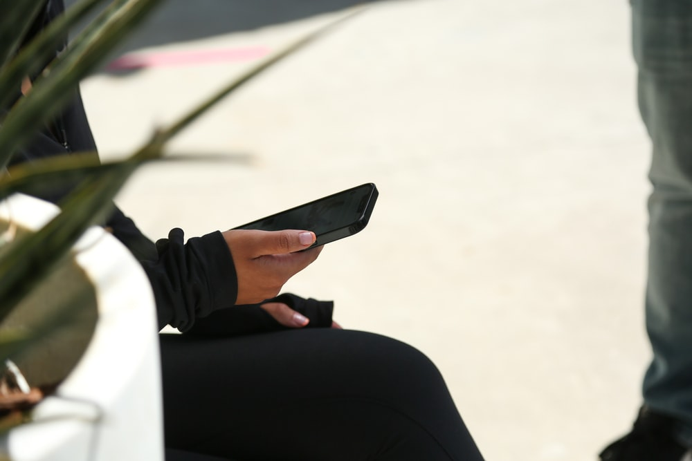 person in black pants holding black smartphone