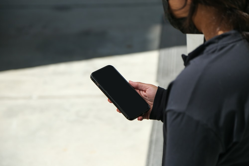 man in black dress shirt holding black smartphone