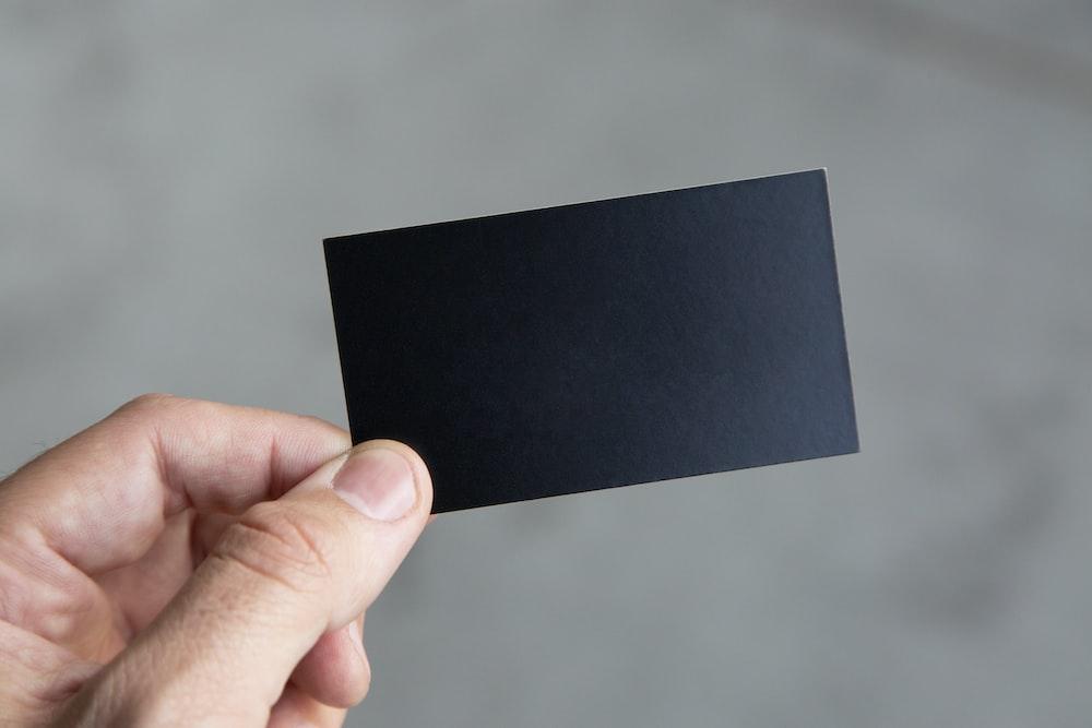 person holding black rectangular paper