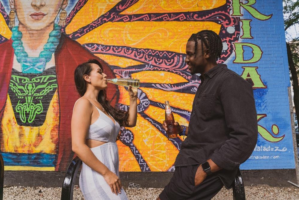 man in black long sleeve shirt kissing woman in white sleeveless dress
