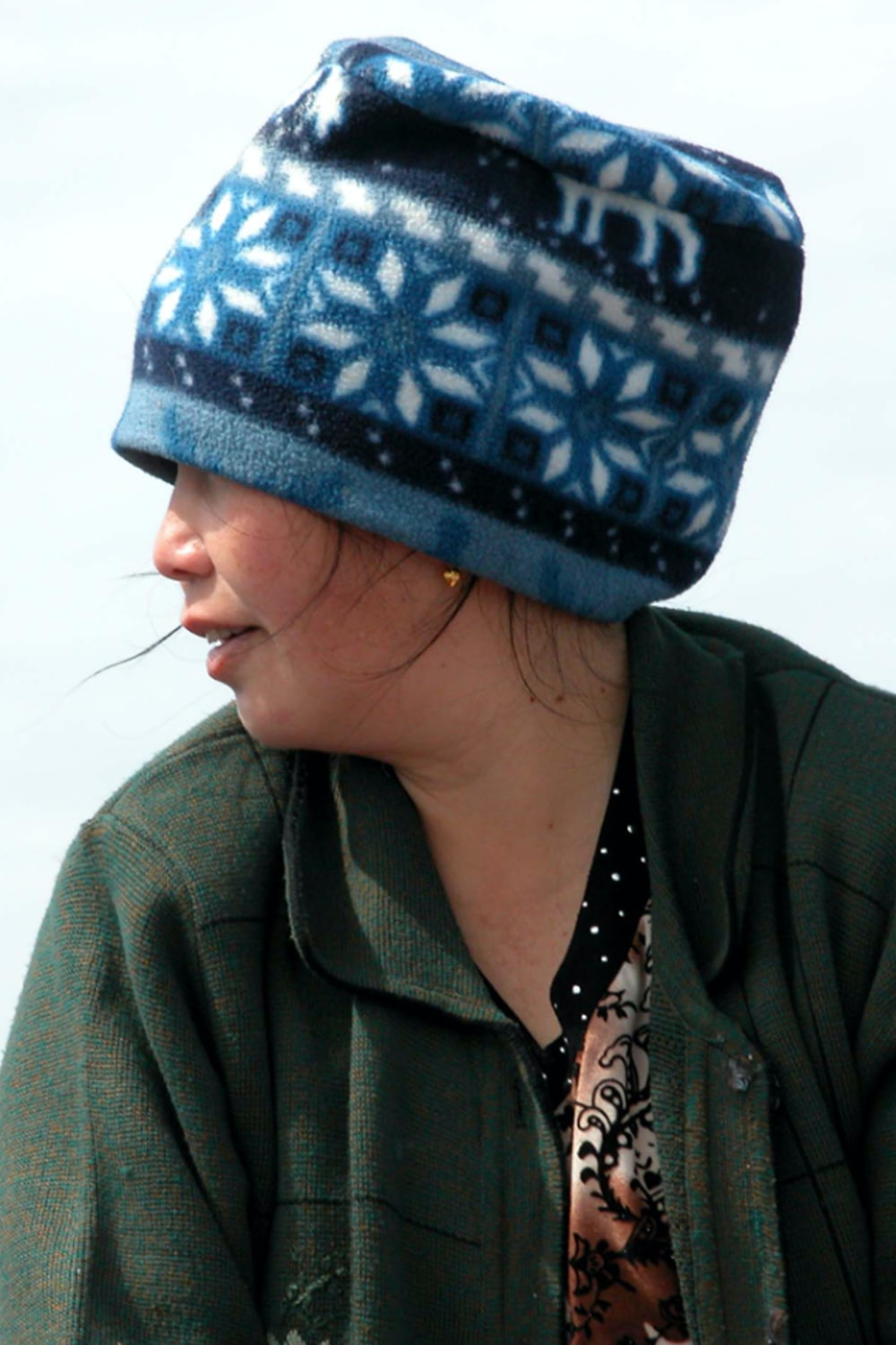 woman in green jacket wearing blue and white knit cap