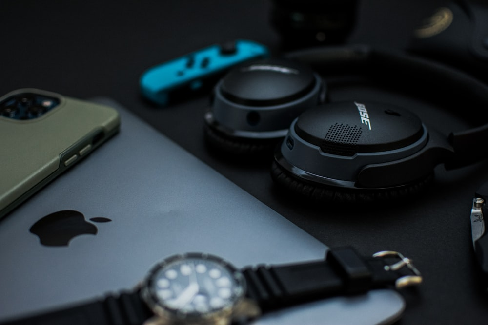 black sony headphones beside blue and red iphone case