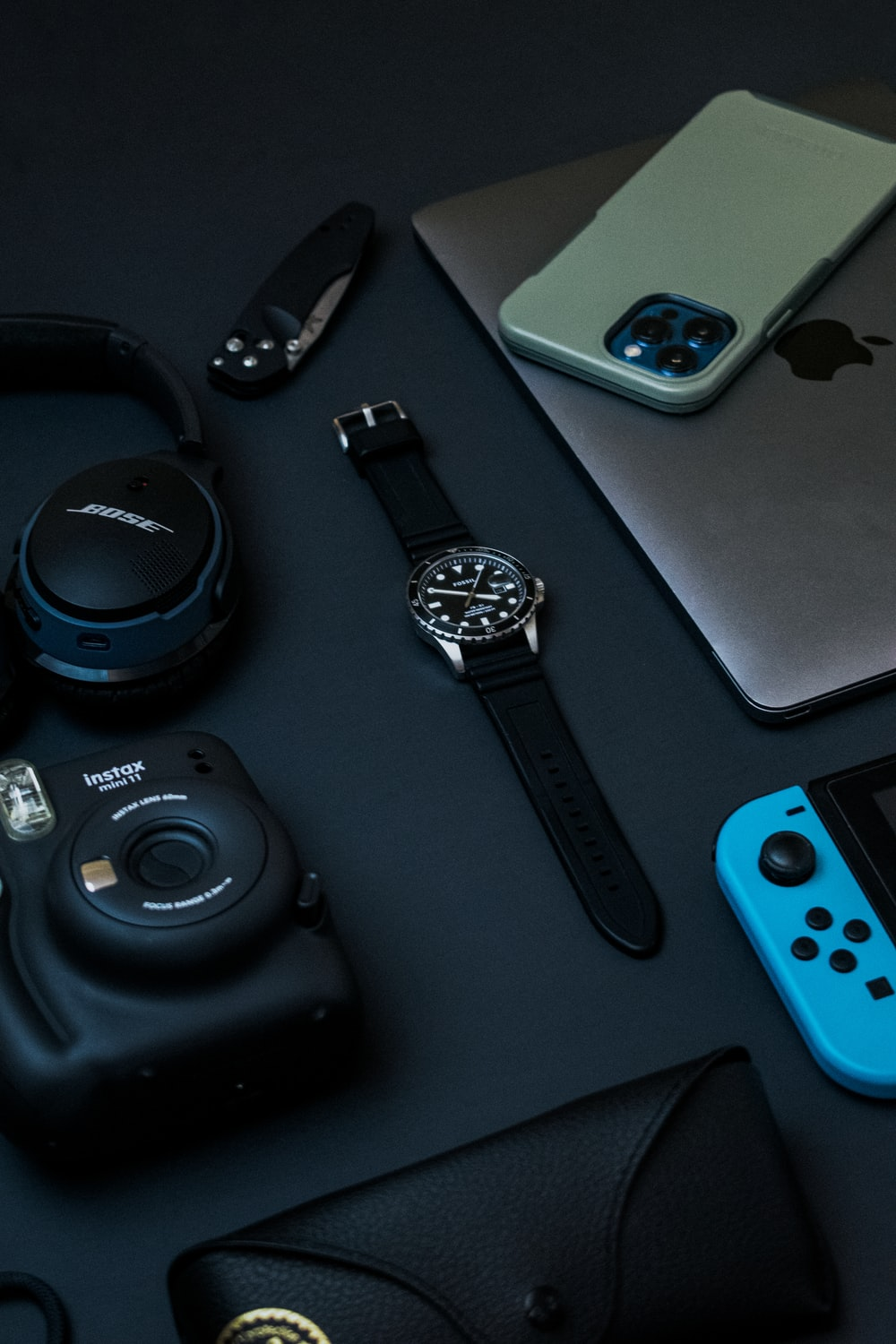 black and silver round analog watch beside silver iphone 6 and black and silver round watch