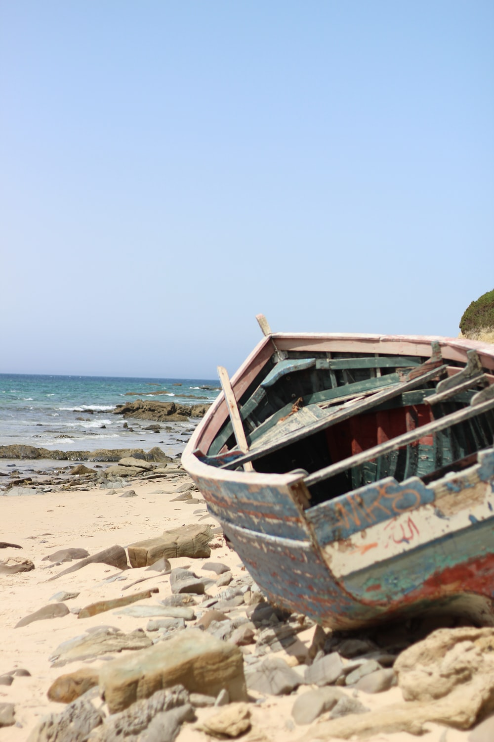 brown and white boat on beach during daytime