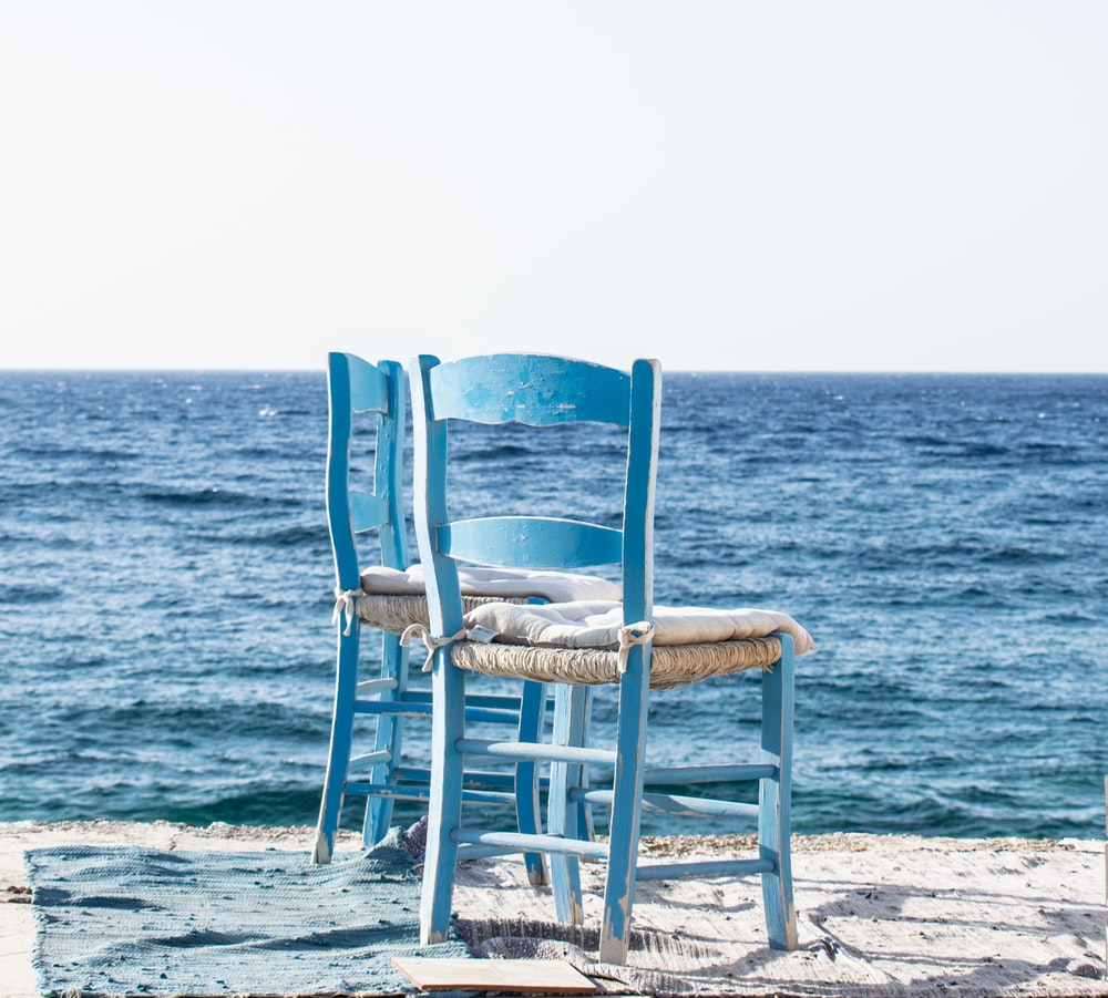 white wooden chair on beach during daytime